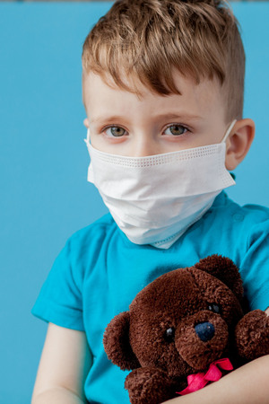 Cute little boy using nebulizer on blue background. Allergy concept.