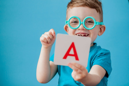 Cute little boy with letter on background. Child learn letters. Alphabet. Stok Fotoğraf