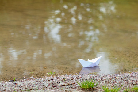 White paper toy boat on blue water near the shore.