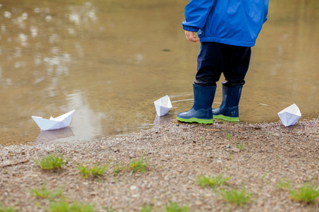 Portrait of cute kid boy playing with handmade ship. kindergarten boy sailing a toy boat by the waters edge in the park.