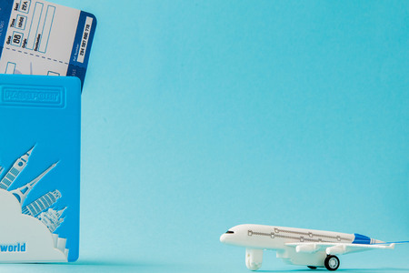Passport, airplane and air ticket on a blue background. Travel concept, copy space.