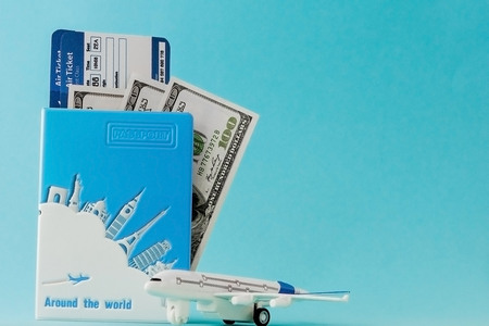 Passport, dollars, plane and air ticket on a blue background. Travel concept, copy space.