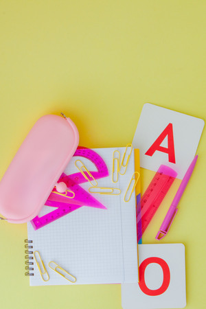 Back to school concept with space for text. Top view. Copy space. School office supplies.Creative desk with colourful stationery. Colored paper clip.School supplies on yellow background.Office desk.