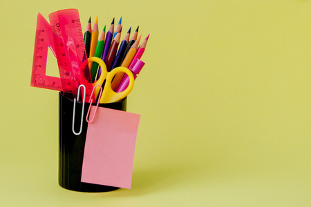 Back to school concept with space for text. Copy space. School office supplies.Creative desk with colourful stationery. Colored paper clip.School supplies on yellow background.Office desk. Stok Fotoğraf