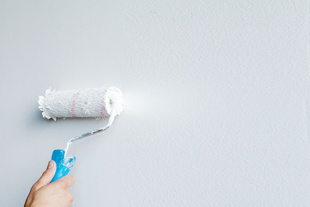 Woman hand holding a paint roller isolated on a white background.