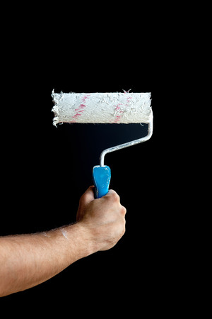 Woman hand holding a paint roller on a black background.