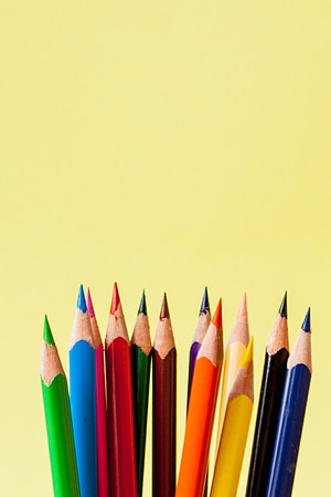 Row of colorful pencils on yellow background.