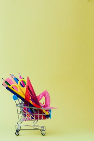 Shopping cart with different stationery on the yellow background. Archivio Fotografico