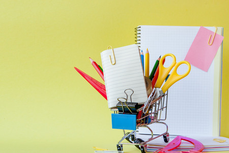 Shopping cart with different stationery on the yellow background. Stok Fotoğraf
