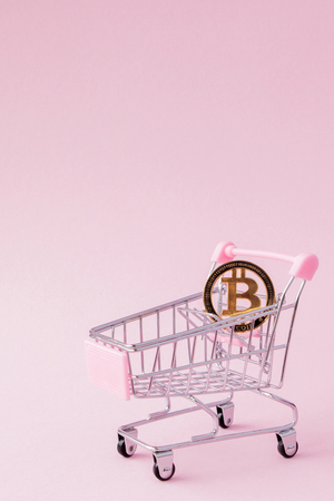 a cart from a supermarket, bitcoin on a wooden background. internet, crypto currency.