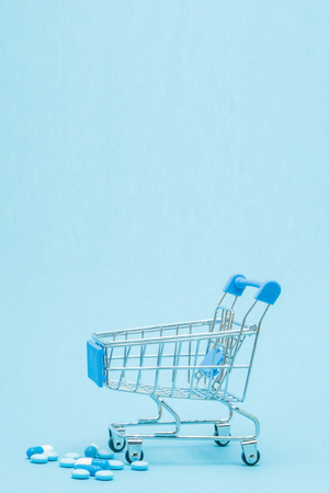 Pills and Shopping trolley on blue background. Creative idea for health care cost, drugstore, health insurance and pharmaceutical company business concept. Copy space.