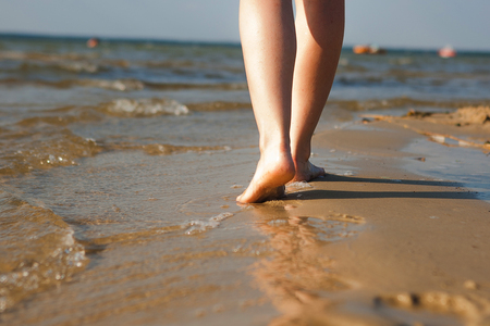 Woman walking on sand beach leaving footprint in the sand. Beach travel. Stok Fotoğraf