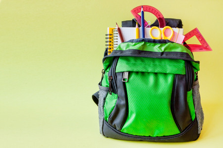Composition with backpack and school stationery on yellow background.