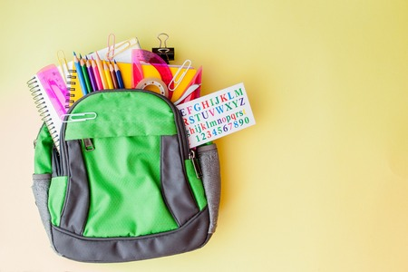 Flat lay composition with backpack and school stationery on yellow background.