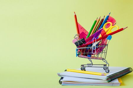 Shopping cart with different stationery on the yellow background. Stock Photo