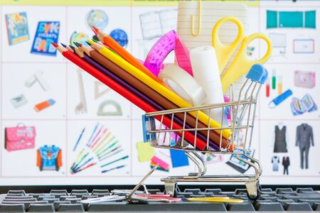 Shopping cart full of school tools on the keyboard, online shopping concept.