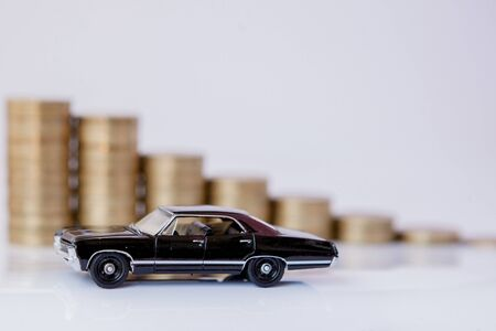 A black model of a car with coins in the form of a histogram on a white background. Concept of lending, savings, insurance