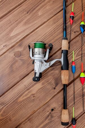 Fishing tackle - fishing rod fishing float and lures on beautiful blue wooden background, copy space. 免版税图像