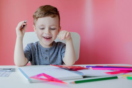 Portrait of cute kid boy at home making homework. Little concentrated child writing with colorful pencil, indoors. Elementary school and education. Kid learning writing letters and numbers.