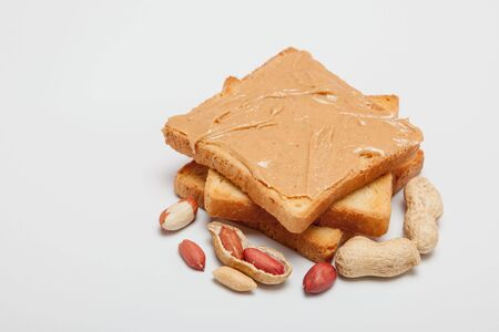 Peanut butter sandwiches or toasts on white background.