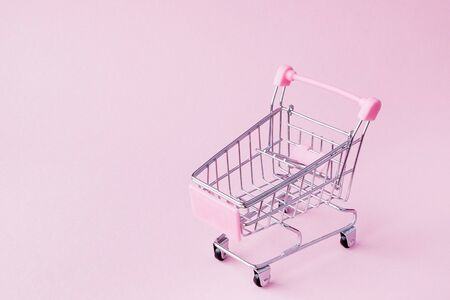 Small supermarket grocery push cart for shopping toy with wheels and pink plastic elements on pink pastel color paper flat lay background. Concept of shopping. Copy space for advertisement.