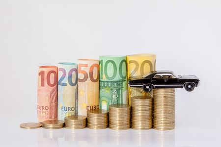 A black model of a car and ten, twenty, fifty, one hundred, two hundred and coins euro rolled bills banknotes on white background. Histogram from the euro. Concept of currency growth, savings