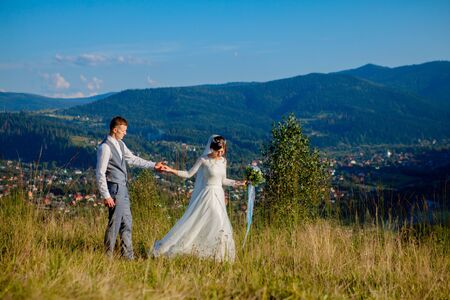 Newlyweds smile and hug each other among the meadow on top of the mountain. Wedding walk in the woods in the mountains, the gentle emotions of the couple, photo for Valentine's Day. Archivio Fotografico