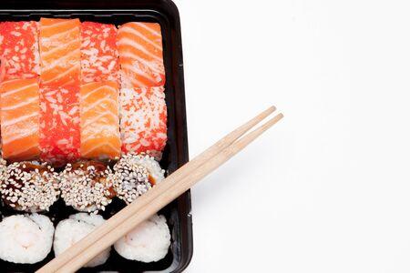 Grande set di sushi ib scatola di plastica nera su sfondo bianco, vista dall'alto ravvicinata, spazio di copia. Archivio Fotografico