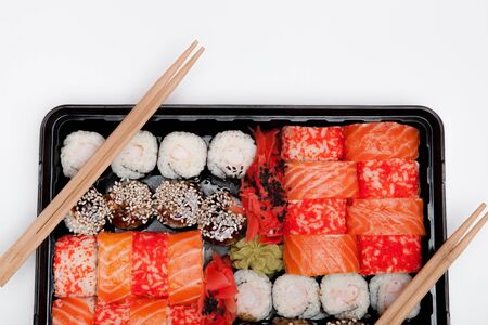 Big sushi set ib black plastic box on white background, top view close up, copy space.