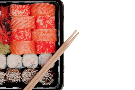 Big sushi set ib black plastic box on white background, top view close up, copy space. Stock fotó