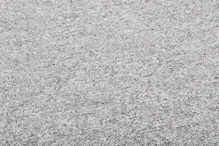 Real tejido de punto gris jaspeado hecho de fibras sintéticas con textura de fondo.