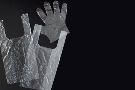 Plastic bag with handles, gloves, on a black background . Used plastic bag for recycling. Concept - ecology, planet pollution with plastic cellophane polyethylene. Stock Photo