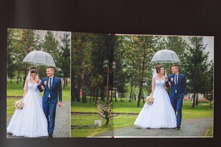Kyiv, Ukraine- May 15, 2019 Pages of wedding photobook or wedding album on black background.