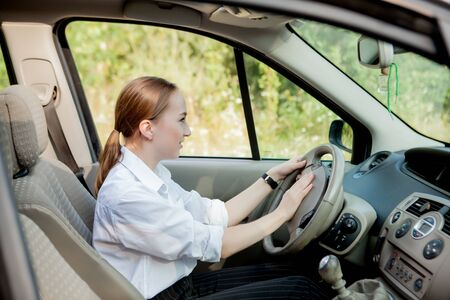 Close up portrait of pleasant looking female with glad positive expression, being satisfied with unforgettable journey by car, sits on driver s seat. People, driving, transport concept. Stok Fotoğraf
