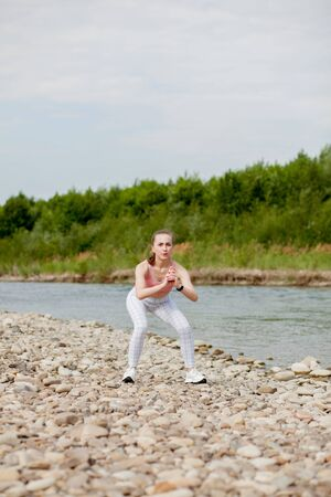 Girl in sports uniforms makes a stretch on the river bank. Banco de Imagens