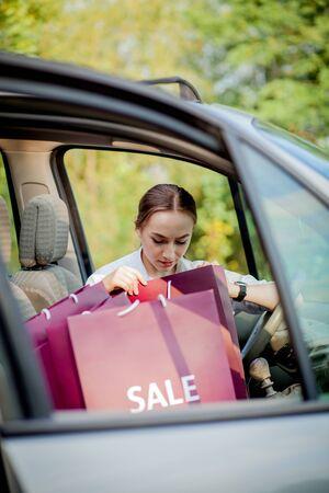Vrouw met haar boodschappentassen in de auto - winkelconcept