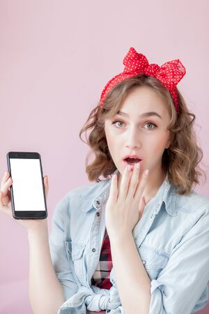Beautiful young woman with pin-up make-up and hairstyle over pink background with mobile phone with copy space