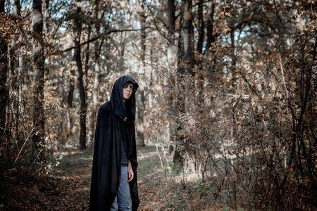 Teenagers in Halloween costumes in the woods. Halloween vampire in the woods.