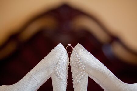 A pair of white wedding shoes with rings on a stool.