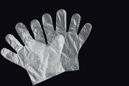 Plastic bag with handles, gloves, on a black background . Used plastic bag for recycling. Concept - ecology, planet pollution with plastic cellophane polyethylene. 版權商用圖片