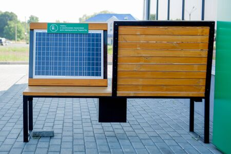 Outdoor shot of wooden bench in park having solar power panel installed, USB cable connected to smartphone.