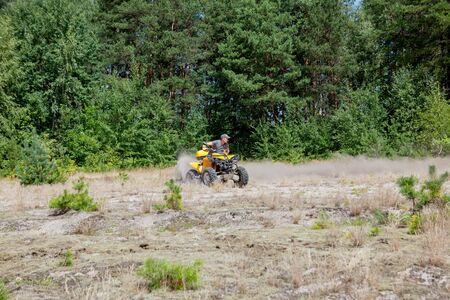 Hombre montado en un vehículo todo terreno quad ATV amarillo en un bosque arenoso. Movimiento de deporte extremo, aventura, atracción turística. Foto de archivo