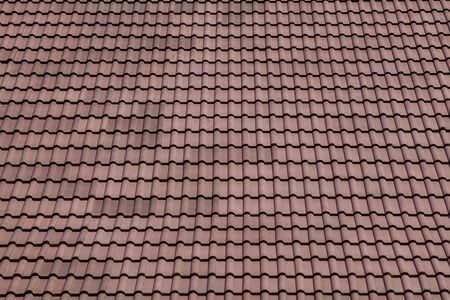 Brown roof with metal tile on blue sky.