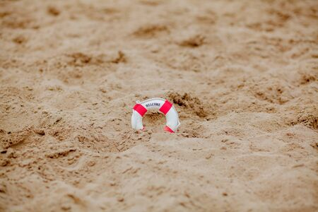 Close-up Of Miniature Lifebuoy Dig In The Sand At Beach. Archivio Fotografico - 129142206