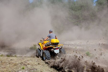 Man riding a yellow quad ATV all terrain vehicle on a sandy forest. Extreme sport motion, adventure, tourist attraction Фото со стока - 129144134