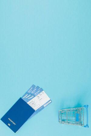 Tickets for airplanes and passport, and shopping cart on a blue background. Copy space for text. Zdjęcie Seryjne
