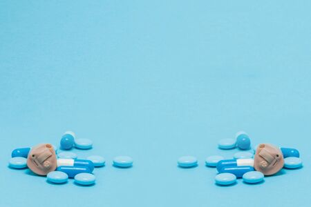 Hearing aid and blue pills on blue background. Medical, pharmacy and healthcare concept.
