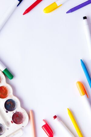 A white sheet of paper lay on a wooden table, near , pencils, paints and markers. Back to school. school and office supplies. education and school border concept and copy space on wooden background. Фото со стока
