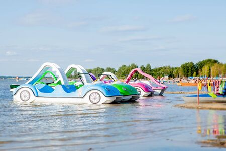 Bright colorful pedal boats at the lake beach.