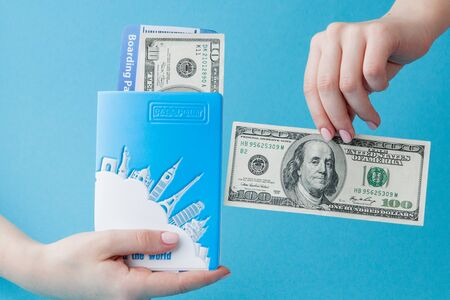 Passport, dollars and air ticket in woman hand on a blue background. Travel concept, copy space. Zdjęcie Seryjne